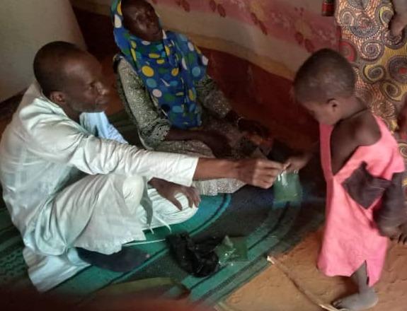 Gao : l'infirmier distribue de la spiruline à un enfant